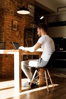 Een man aan het werk op een computer vanuit huis