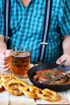 Een man aan tafel met een glas bier, een krakeling en een koekenpan met worstjes. oktoberfest-viering.