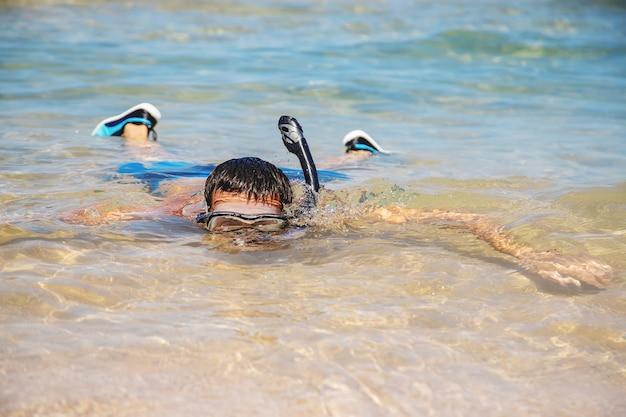 Een man aan zee in vinnen en masker.