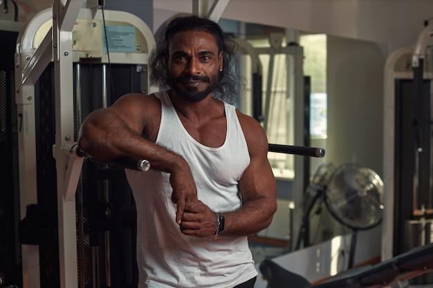 Een man atleet lankian met gegolfd haar staat in de sportschool en kijkt recht in de camera met hoge qu...