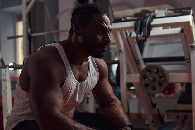 Een man-atleet met een donkere huid zit in de sportschool en kijkt uit naar sport en een gezond levensstijlconcept h...