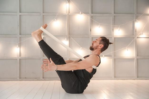 Een man beoefent yoga in een lichte studio. man en yoga asanas met elastiek.