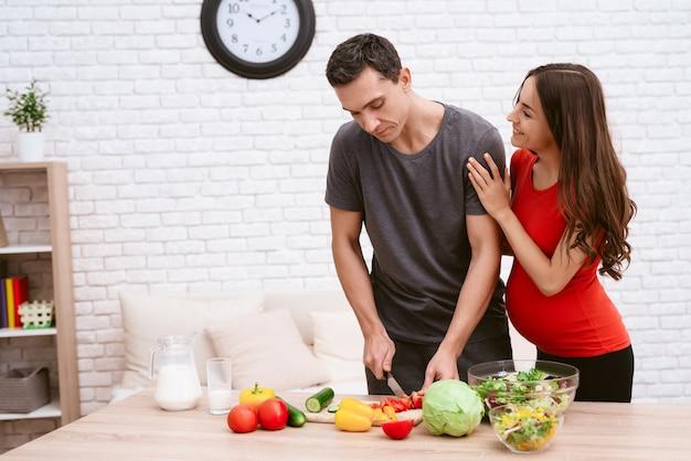 Een man bereidt gezond voedsel voor zijn zwangere meisje.