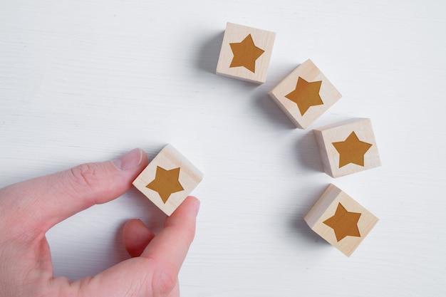 Een man besluit met zijn hand vijf sterren te plaatsen of niet op houten kubussen met de beste beoordeling. beste score. plat leggen.