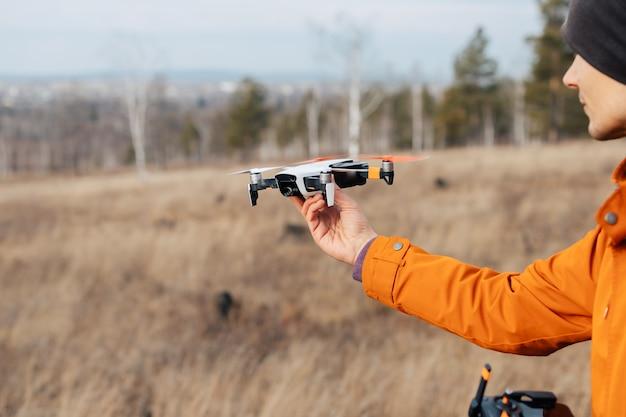 Een man bestuurt een quadcopter-drone buiten in de herfst. de man steekt zijn hand uit naar de drone.