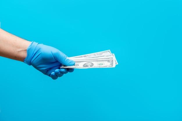 Een man betaalt geld in een rubberen handschoen. coronavirus bescherming. overdracht van het virus via geld.
