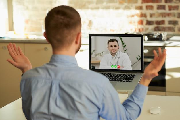 Een man bij de afspraak van de dokter tijdens een videogesprek op zijn laptop thuis.