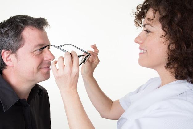 Een man bij de opticien probeert zijn nieuwe bril
