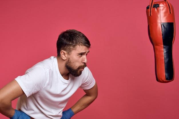 Een man bij een bokszak in blauwe handschoenen en een wit t-shirt oefent sportstoten.
