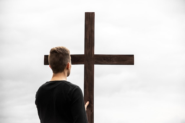 Een man bij het kruis. de mens gelooft in god. hoop op god