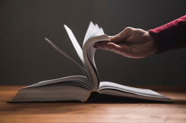 Een man bladert door de pagina's van een boek op een donkere ondergrond