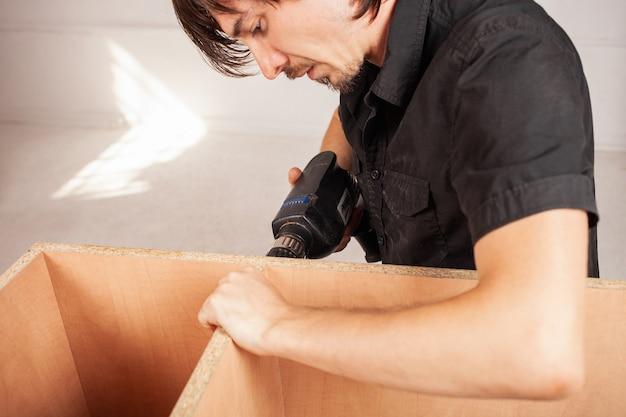 Een man boort met een boor een gat in een kast. kabinet.