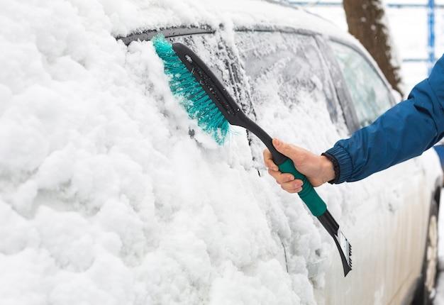 Een man borstelt sneeuw uit een auto na een sneeuwval. een hand in een blauw jasje met een autobezem op het witte lichaam. winter weersomstandigheden