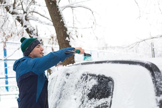 Een man borstelt sneeuw uit een auto na een sneeuwval.