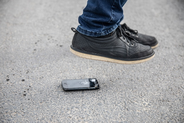 Een man breekt de telefoon met zijn voet op het asfalt