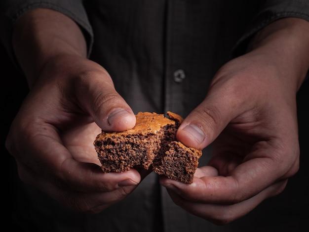 Een man breekt een stuk browniekoekjes.