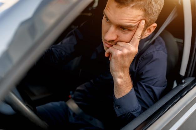Een man brengt veel tijd door in de file om van huis naar kantoor te komen. hij verveelt zich en is teleurgesteld