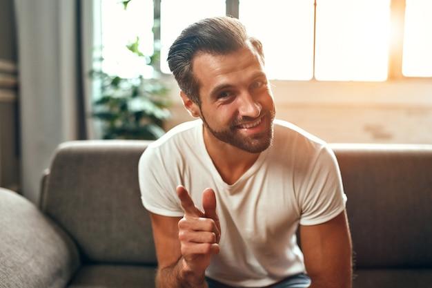 Een man communiceert via een videogesprek terwijl hij thuis op de bank in de woonkamer zit. werk vanuit huis.
