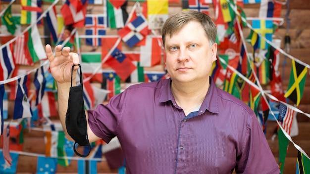 Een man deelt een gebruikt medisch masker in zijn handen tegen de achtergrond van landvlaggen