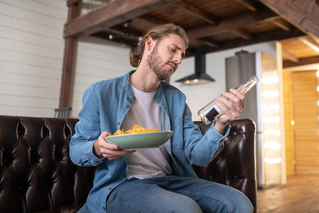 Een man die bier drinkt en friet eet terwijl hij thuis blijft