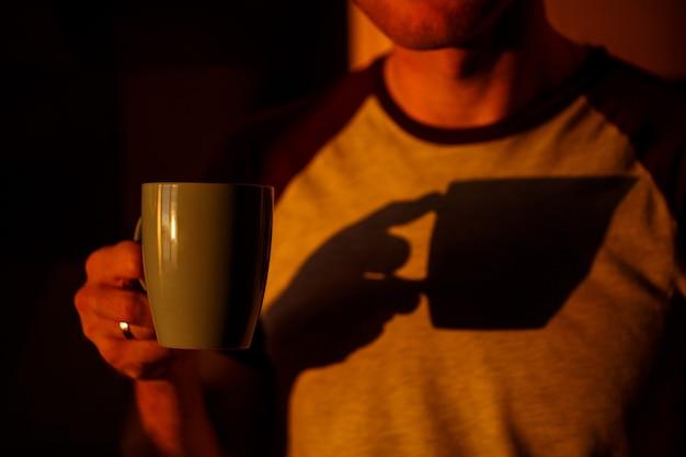 Een man die bij zonsondergang voor een raam staat, drinkt koffie in zijn keuken
