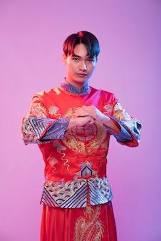 Een man die cheongsam draagt, staat en respecteert de klant die in chinees nieuwjaar komt winkelen