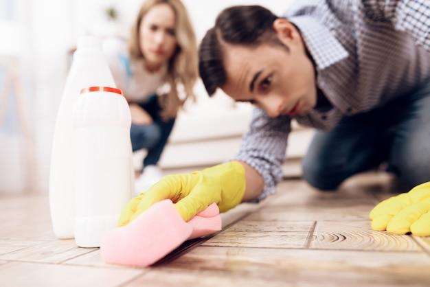 Een man die de vloer in het appartement van een vrouw schoonmaakt.