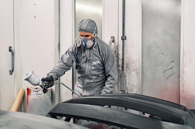 Een man die een auto schildert