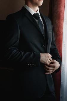Een man die een blauwe jas dichtknoopt