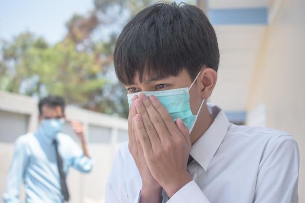 Een man die een chirurgisch masker draagt om zijn neus te bedekken met hoesten en niezen door ziekte om de verspreiding van virussen en ziektekiemen naar anderen te voorkomen, gebruiken aziatische thaise mensen een gezichtsmasker als ze ziek zijn