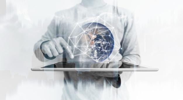 Een man die een digitale tablet gebruikt met een wereldwijd hologram voor netwerkverbindingstechnologie.