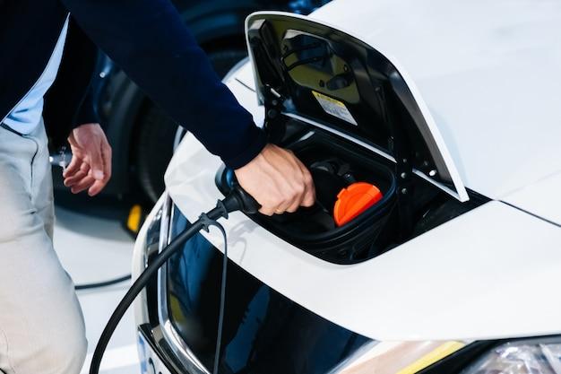 Een man die een elektrische auto oplaadt