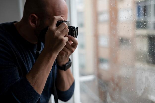 Een man die een foto neemt met een analoge camera door een raam