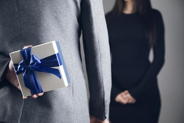 Een man die een geschenk van achteren vasthoudt terwijl hij voor een meisje staat