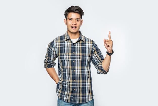Een man die een gestreept overhemd draagt en naar de top wijst