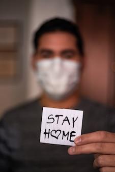 Een man die een gezichtsmasker draagt en een stuk papier vasthoudt met het opschrift ''blijf thuis''