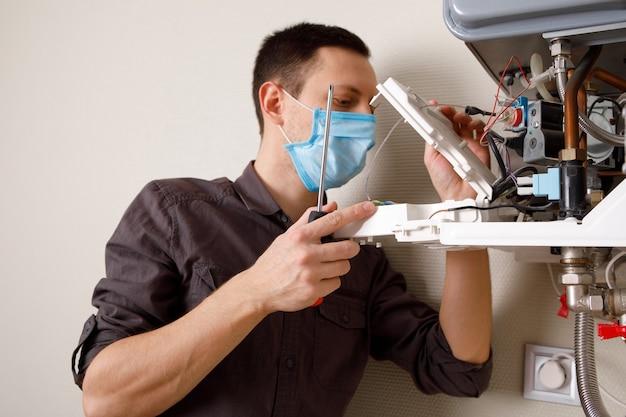 Een man die een ketel in een medisch masker herstelt