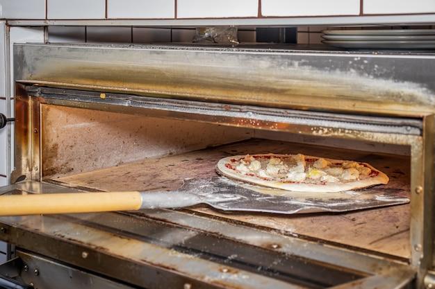 Een man die een margherita-pizza maakt in een lokaal pizza- en gyrosrestaurant