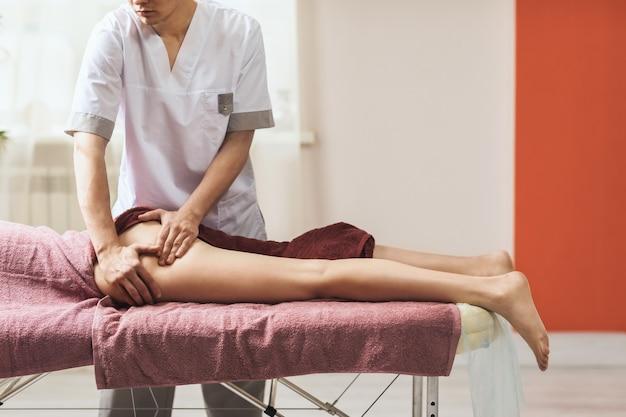 Een man die een massage uitvoert op de dij- en bilspieren in zijn kantoor