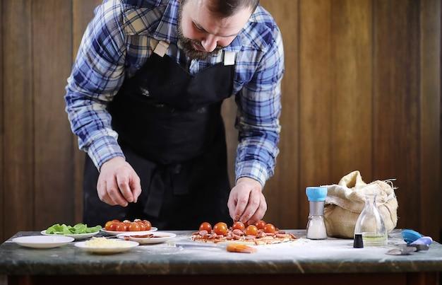 Een man die een pizza bereidt, het deeg kneedt en ingrediënten erin doet