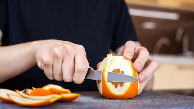 Een man die een sinaasappel pelt met een mes op een kookplank