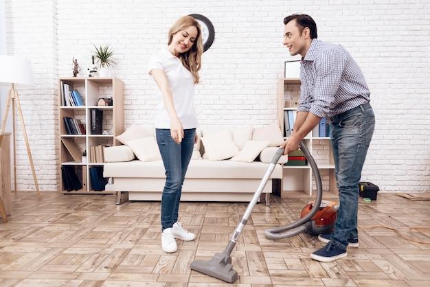 Een man die een stofzuiger in de kamer van een vrouw schoonmaakt.