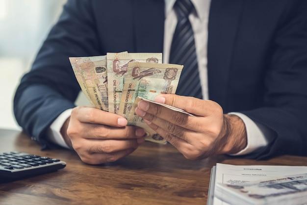 Een man die geld telt, bankbiljetten van de vae aan zijn bureau
