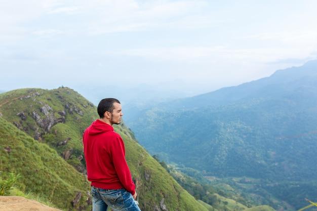 Een man die geniet van het berglandschap aan de rand van een klif