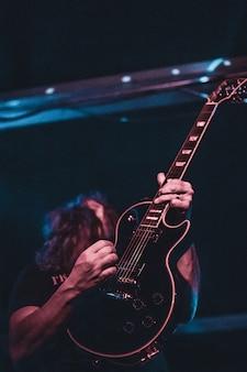 Een man die gitaar spelen op het podium. donkere achtergrond, schijnwerpers.