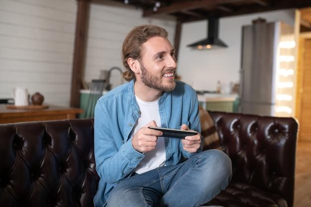 Een man die graag thuis een nieuwe videogame speelt