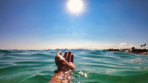 Een man die hand boven het water houdt, middellandse zee