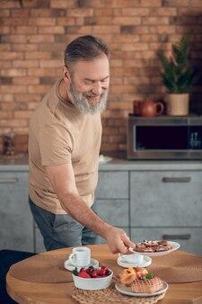 Een man die het ontbijt klaarmaakt en er betrokken uitziet