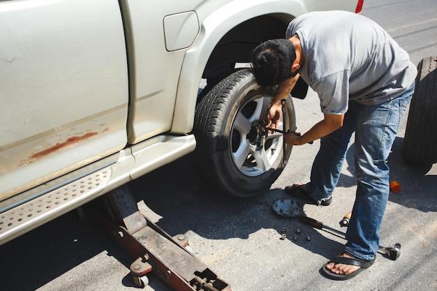 Een man die het wiel aan de kant van de weg verwisselt