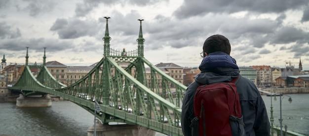 Een man die hoog zit kijkt naar een groene brug in boedapest (hongarije)